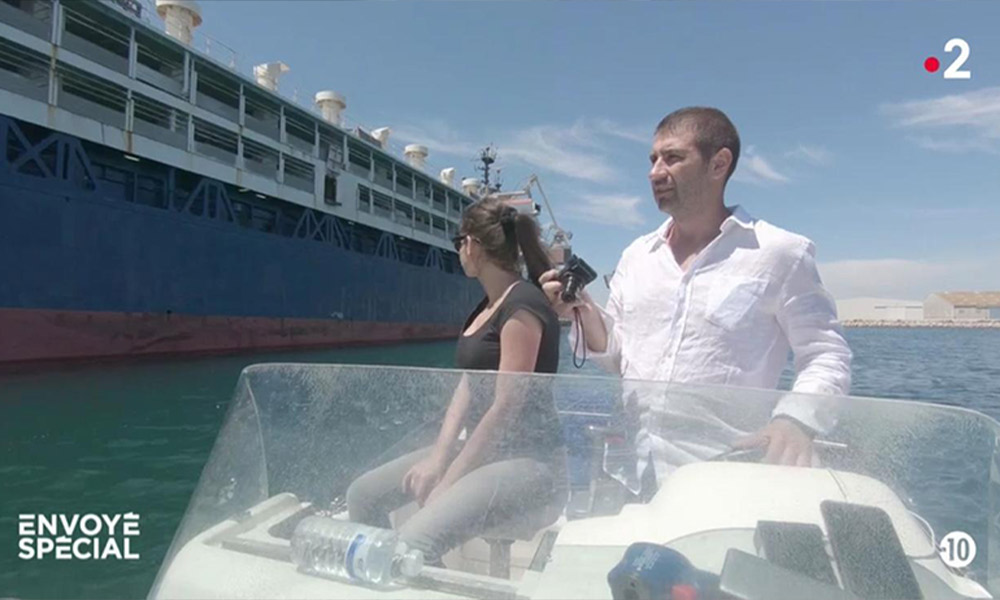 Gabi Paun on a speedboat with a journalist next to a live export ship