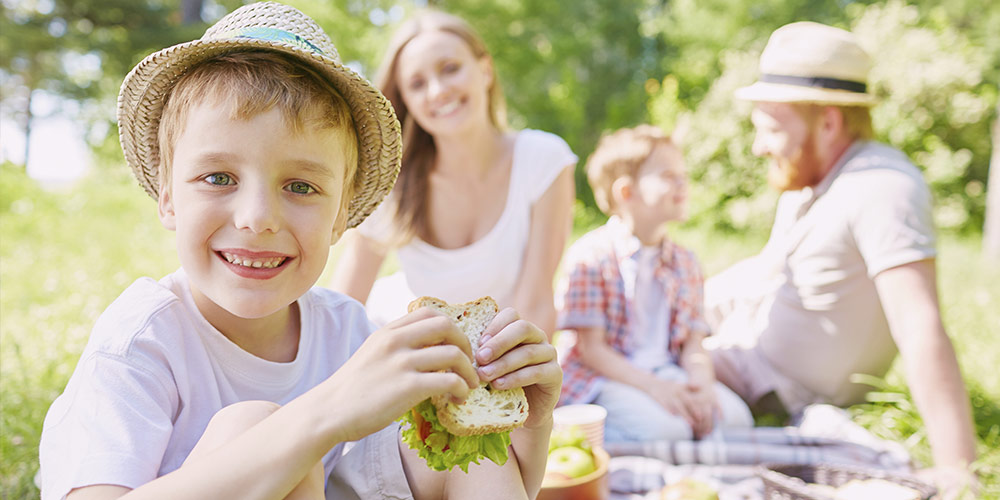 Little boy eating a sandwich at a family picnic