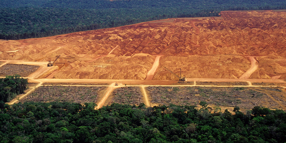 Wide brown swathe of cleared land in rainforest